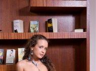 Голая девушка позирует в библиотеке
