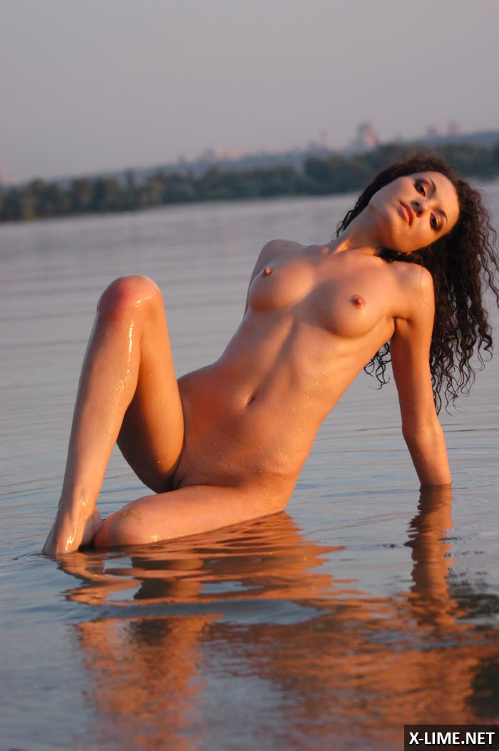 Голая кудрявая брюнетка в эротической фотосессии