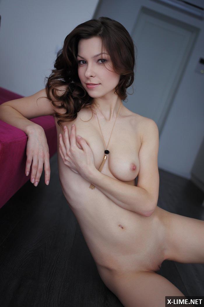 Голая шатенка позирует на малиновом диване, эротические фото