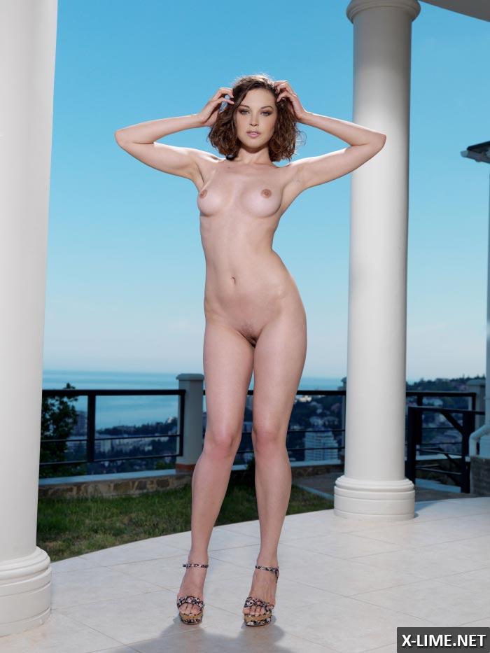 Стройная девушка обнажилась на террасе с видом на море