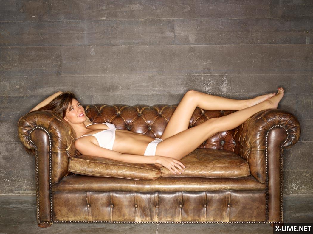 Голая стройная девушка позирует на кожаном диване