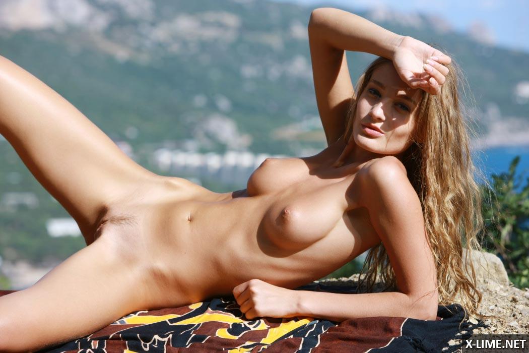 Молоденькая блондинка позирует в горах