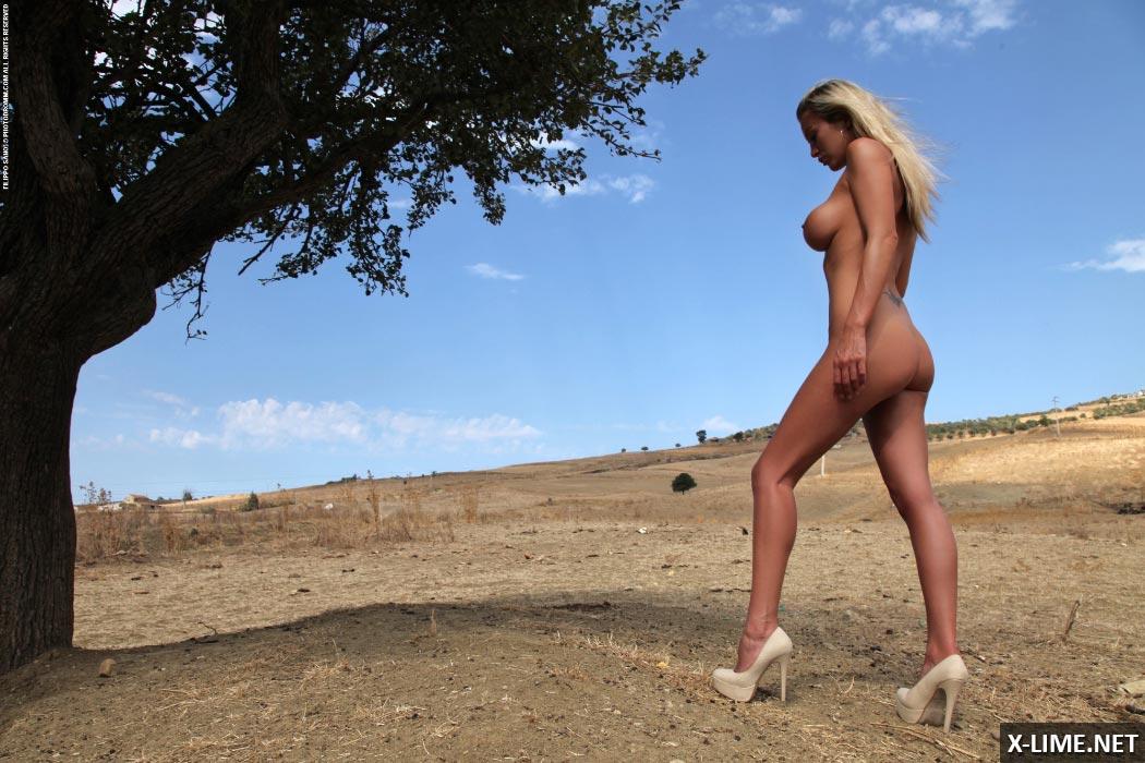 Голая блондинка с большими сиськами на природе