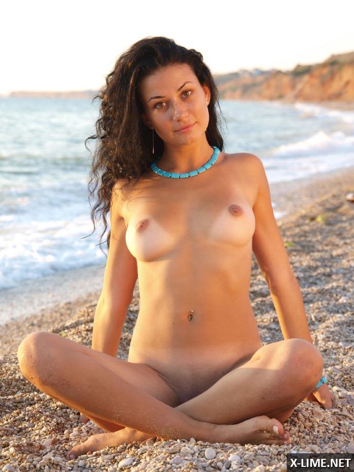 Молодая девушка позирует голышом на пляже